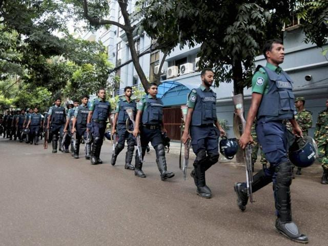 Bangladeshi policemen patrol the area around the site of an attack in Dhaka.