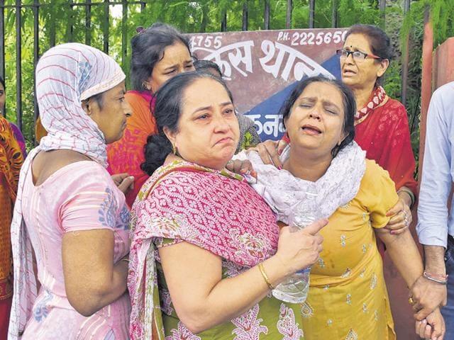 Vishnu Lekhwani's wife (in yellow) breaks down outside Ashok Nagar police station during a protest.