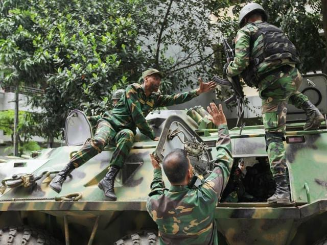 Armoured vehicles arrive after militants took hostages at a restaurant popular with foreigners in Dhaka.