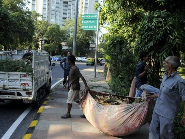 NDMC workers collect garbage from a street in New Delhi.