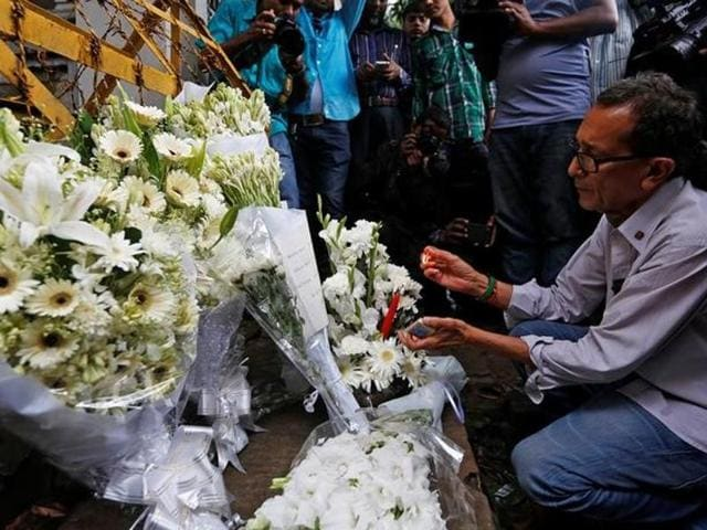 A man lights a candle at a makeshift memorial, to pay tribute to the victims of the attack on the Holey Artisan Bakery and the O'Kitchen Restaurant, near the site of the attack in Dhaka, Bangladesh.