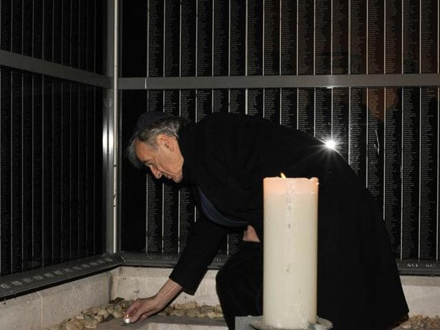 Elie Wiesel lights a candle for Holocaust victims on a memorial wall, which identifies tens of thousands of Hungarian Holocaust victims in Budapest.