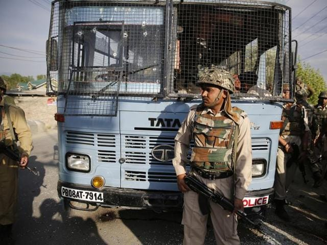 Security personnel stand guard near a damaged bus that was carrying paramilitary soldiers after a highway ambush by militants in Pampore on the outskirts of Srinagar on June 25, 2016.