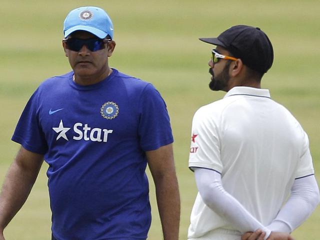 Indian cricket team captain Virat Kohli, right, and head coach Anil Kumble walk past each other.