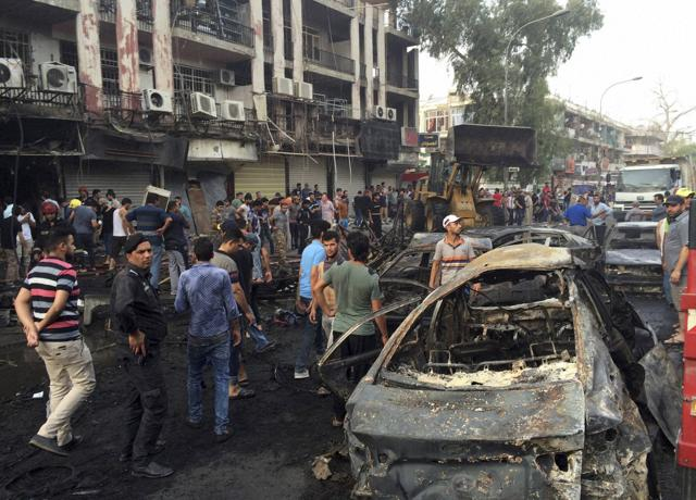 People gather at the site of a suicide car bomb in the Karrada shopping area in Baghdad.