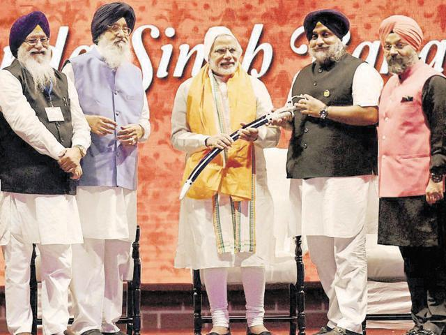 Deputy CM Sukhbir Singh Badal presenting a sword to Prime Minister Narendra Modi as CM Parkash Singh Badal looks on at the Banda Singh Bahadur martyrdom function in New Delhi on Sunday.