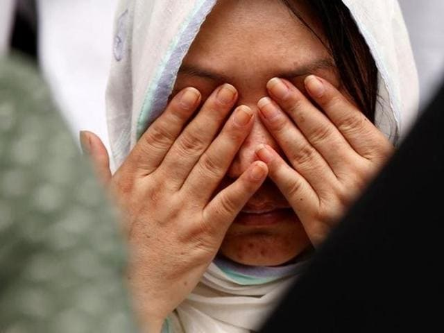 A relative wipes her tears after seeing the coffin of a victim who was killed in the attack on the Holey Artisan Bakery and the O'Kitchen Restaurant, during a memorial ceremony in Dhaka.