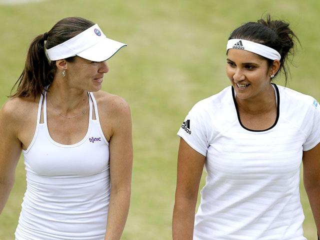 Martina Hingis of Switzerland, left, and Sania Mirza of India talk between points.