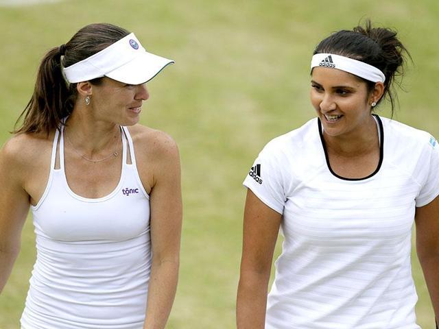 Martina Hingis of Switzerland, left, and Sania Mirza of India talk between points.