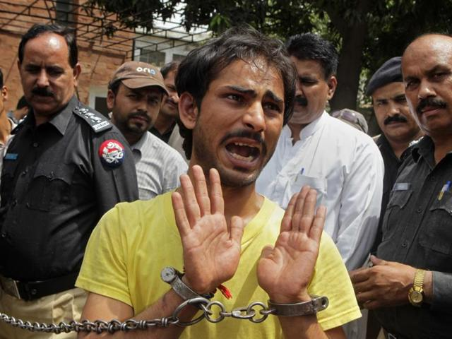 In this file photo, Anees, brother of 18-year-old Zeenat, who was killed by her mother, talks to reporters while under arrest for aiding in the murder, in Lahore, Pakistan.