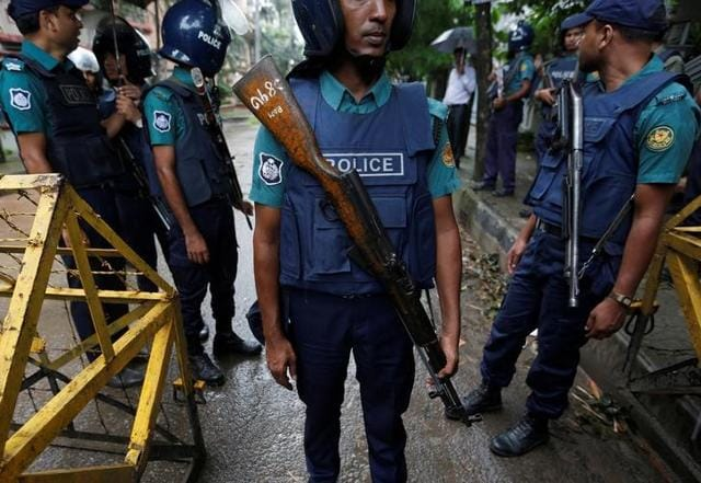Policemen stand guard along a road leading to the Holey Artisan Bakery and the O'Kitchen Restaurant after the attack in Dhaka, on Sunday.
