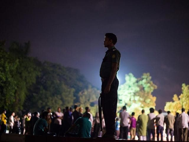 A Bangladeshi policeman keeps guard near a group of peace activists who had come together to sing and light candles in a park following an attack and seige in Dhaka .