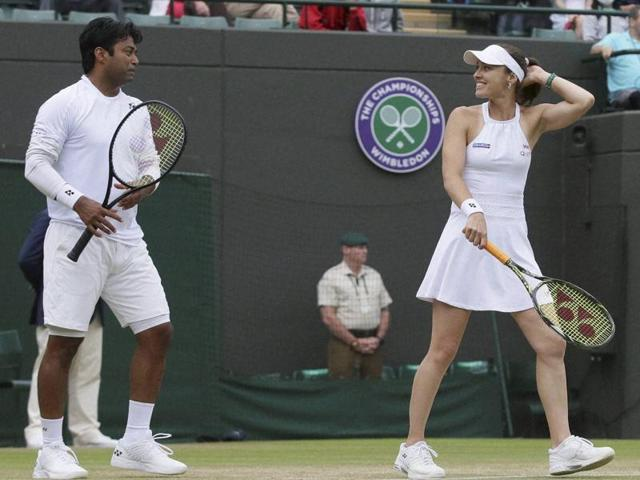 Martina Hingis of Switzerland with playing partner Leander Paes speak during their mixed double match against Laura Siegemund of Germany and Artem Sitak of New Zealand on day eight of the Wimbledon Tennis Championships in London.