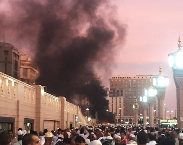 In this photo provided by Noor Punasiya, people stand by an explosion site in Medina, Saudi Arabia.
