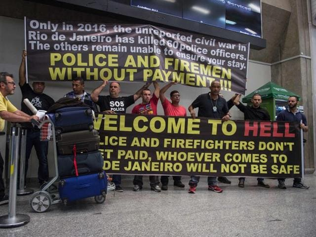 Police officers welcome passengers with a banner reading