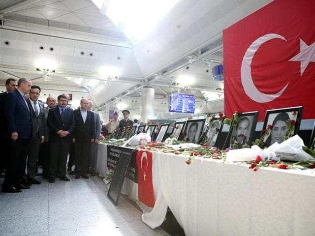 Turkish President Tayyip Erdogan (left) looks at pictures of Ataturk airport employees who were killed in Tuesday's attack on the airport.