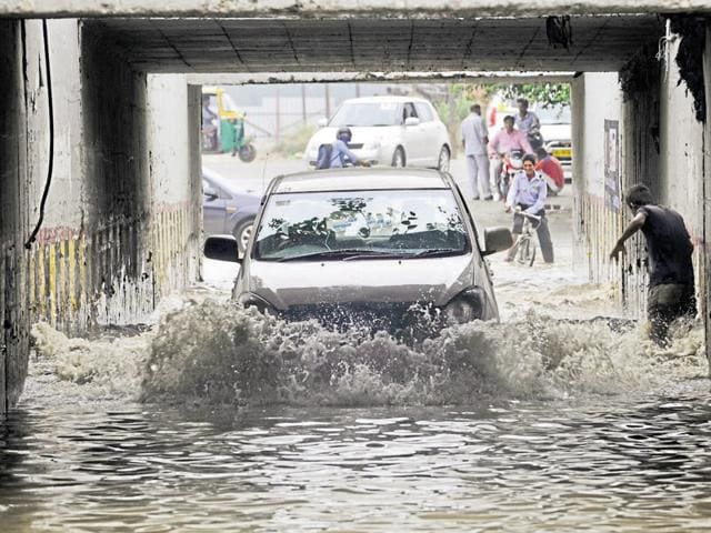 Motorists and pedestrians wade their way through a waterlogged Hajipur subway in Noida on Monday.