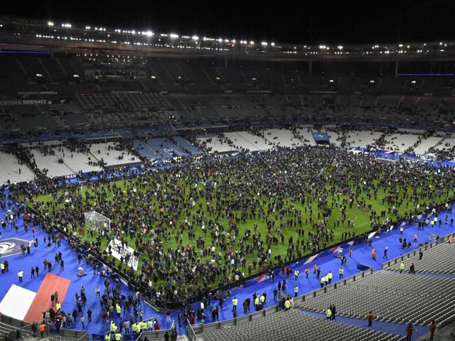 Spectators gather on the pitch of the Stade de France stadium following the friendly football match between France and Germany in Saint-Denis, north of Paris, after a series of gun attacks occurred across Paris as well as explosions outside the national stadium where France was hosting Germany.