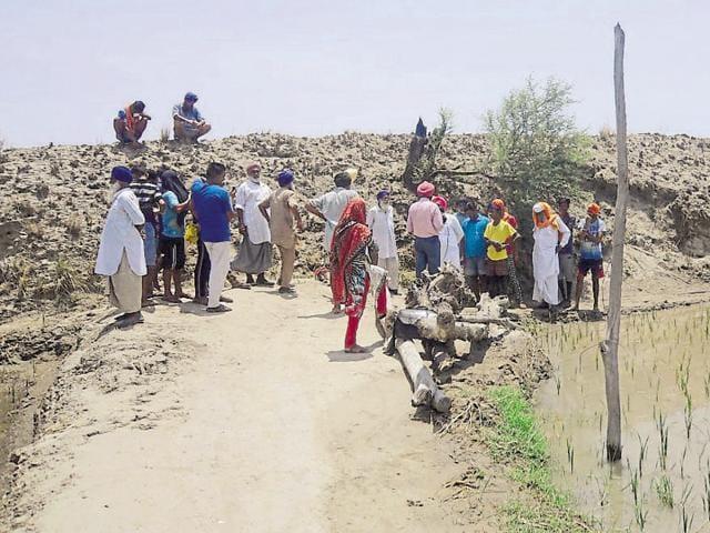 Farmers near the embankment built by the army during the Kargil War to strengthen defences at Khemkaran district in Tarn Taran.