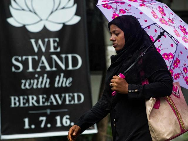 A Bangladeshi woman walks past a banner that reads
