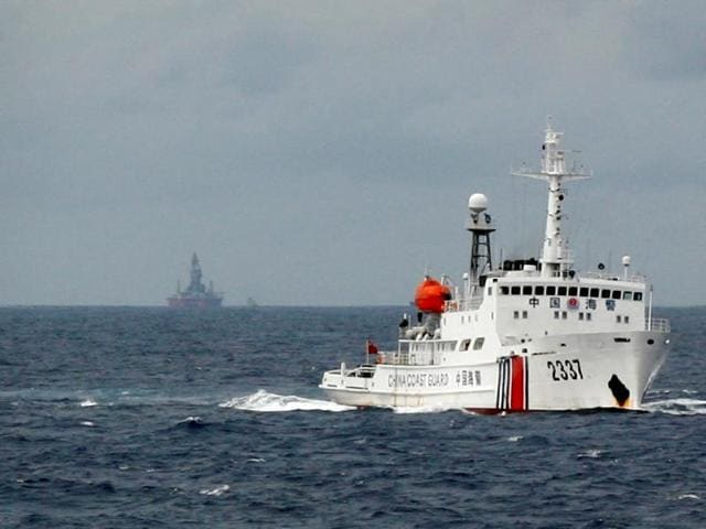 A Chinese Coast Guard vessel (R) passes near the Chinese oil rig, Haiyang Shi You 981 (L) in the South China Sea June 13, 2014.