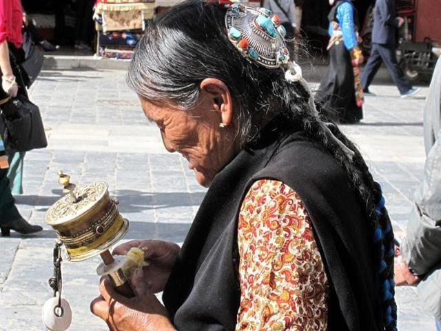 A Tibetan woman rolls a row of prayer wheels near Jokhang Temple in Lhasa, Tibet Autonomous Region, China.