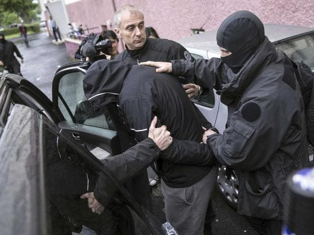This May 13, 2014 file photo shows French police officers detaining a suspect during a raid in a Strasbourg suburb, eastern France.