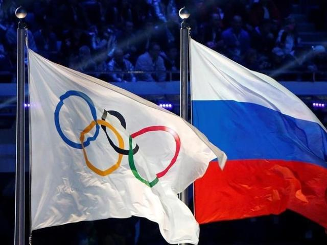 The Russian national flag (right) and the Olympic flag are seen during the closing ceremony during the 2014 Sochi Winter Olympics, Russia.