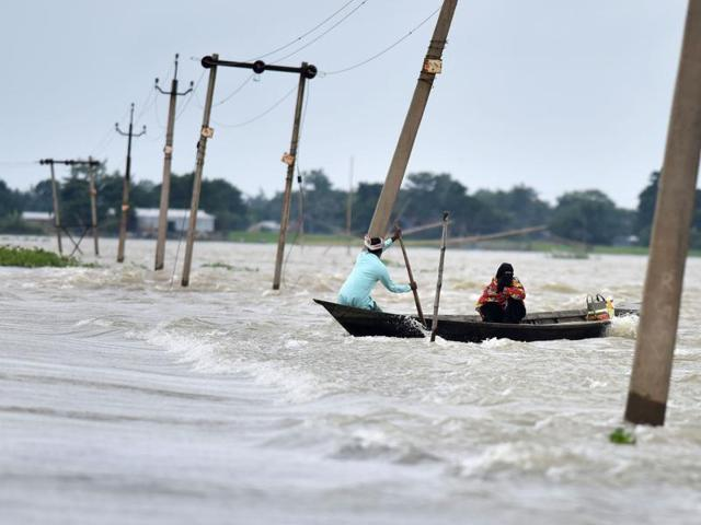 Villagers paddle a boat along a submerged road in the flood-affected Ashighar village in Assam.