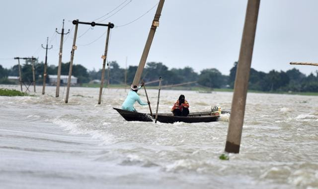 Indian villagers paddle a boat along a submerged road in the flood-affected Ashighar village in Assam on Tuesday.