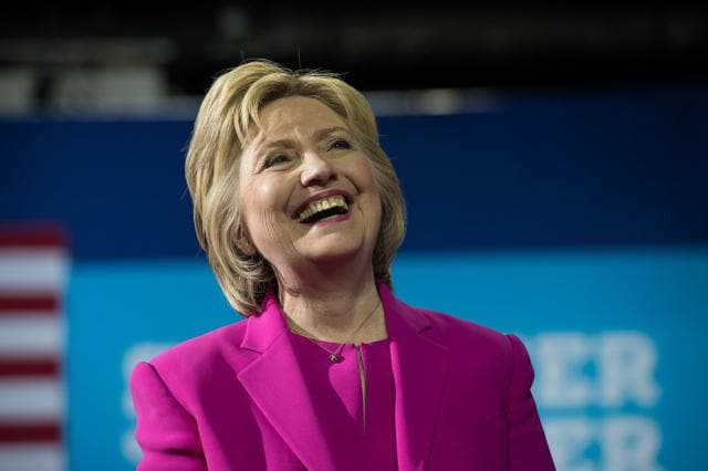 US Democratic presidential candidate Hillary Clinton laughs as President Barack Obama speaks at a campaign event for in Charlotte, North Carolina, on July 5, 2016. US President Barack Obama threw his full weight behind Hillary Clinton's bid to succeed him, extolling the experience and fighting spirit of his former secretary of state at their first joint campaign appearance.