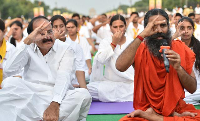 Yoga exponent Ramdev and Union Minister Venkaiah Naidu practice Yoga along with others during a yoga camp at Rajpath in New Delhi.