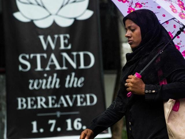 A woman walks past a banner that reads