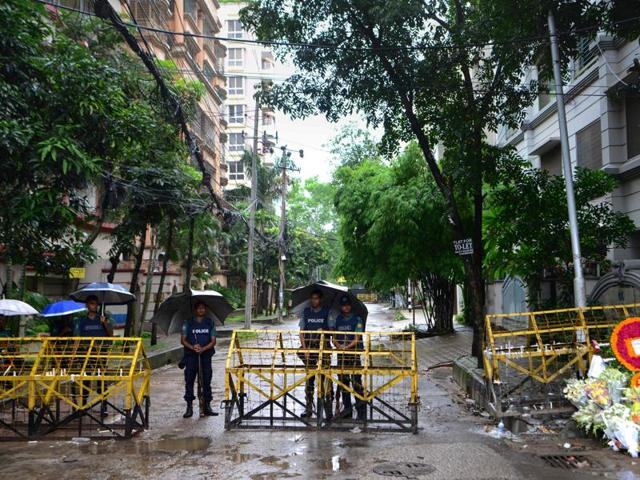 Policemen stand under umbrellas at a checkpoint in Dhaka.