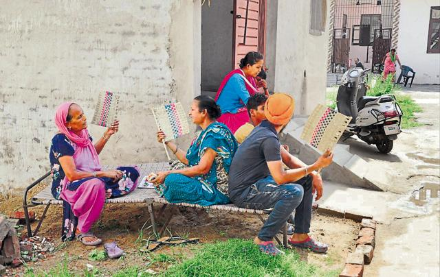 Residents of the Rose Garden colony sitting in the open due to low voltage in their area in Jalandhar.