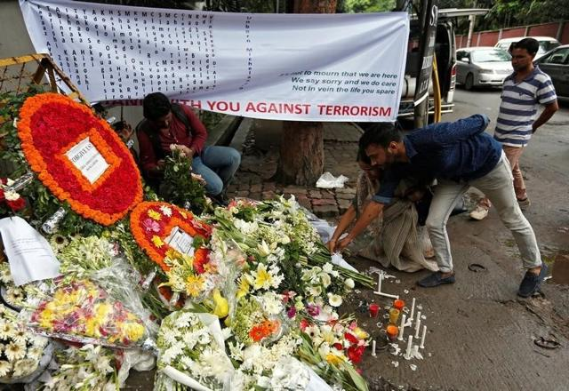 People place flowers at a makeshift memorial near the site, to pay tribute to the victims of the attack on the Holey Artisan Bakery and the O'Kitchen Restaurant, in Dhaka on Tuesday.