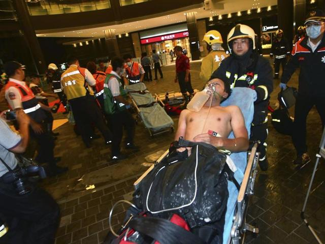 Injured people are helped by emergency rescue workers after an explosion on a passenger train in Taipei, Taiwan.