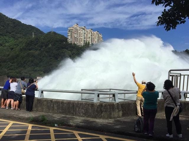 This handout photo taken by the Water Resources Agency and released by CNA Photo on Thursday shows visitors watching as water is released as a preventive measure from the Shihmen Dam in the northern city of Taoyuan as weather forecasters warn of torrential rains and fierce winds from approaching Super Typhoon Nepartak.