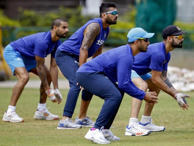 Indian cricket team captain Virat Kohli (right) and teammates take their positions to catch the ball on the last day of team's six day training camp at National Cricket Academy in Bangalore.