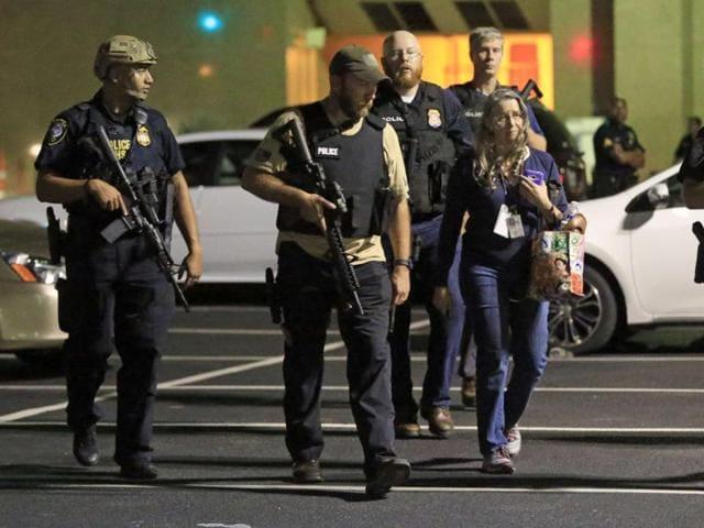 Dallas police officers escort a woman near the scene where eleven Dallas police officers were shot .