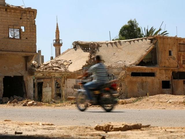 A man rides a motorbike past damaged buildings along a street in the rebel-held town of Dael, in Deraa Governorate, Syria.(REUTERS)