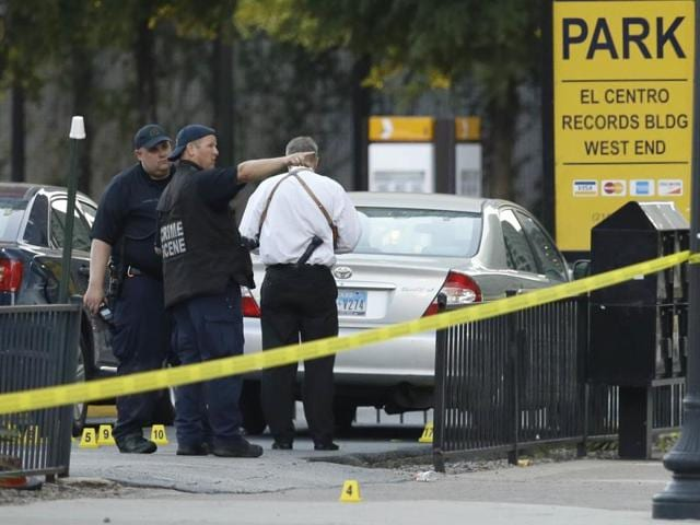 Crime scene investigators survey an area after a shooting in downtown Dallas.