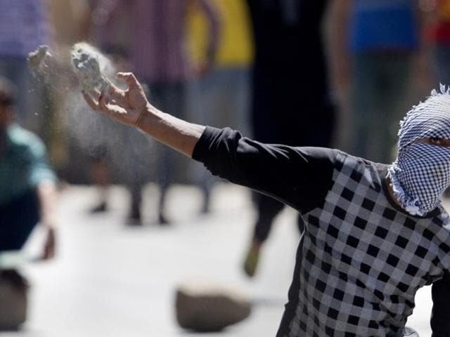 A protester throws a rock at policemen in Srinagar. Afspa, a law which gives security forces sweeping powers, was imposed in Kashmir in 1990.