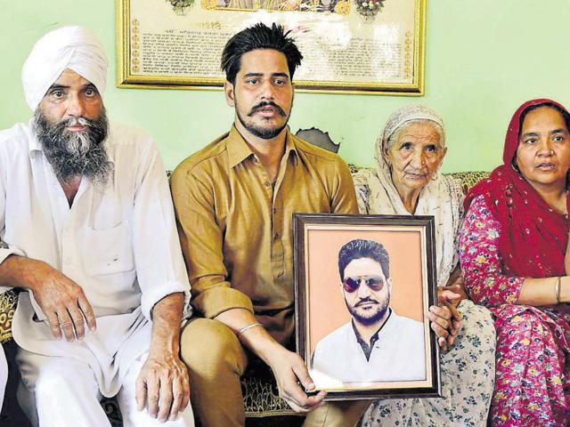 Family members of deceased Mukhjit Singh Mukha with his photograph at Verka village in Amritsar on Thursday.