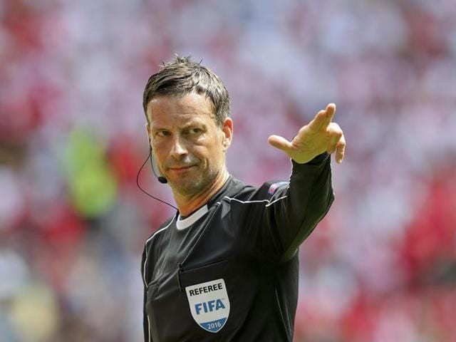 Referee Mark Clattenburg shows a yellow card to Poland's Michal Pazdan.