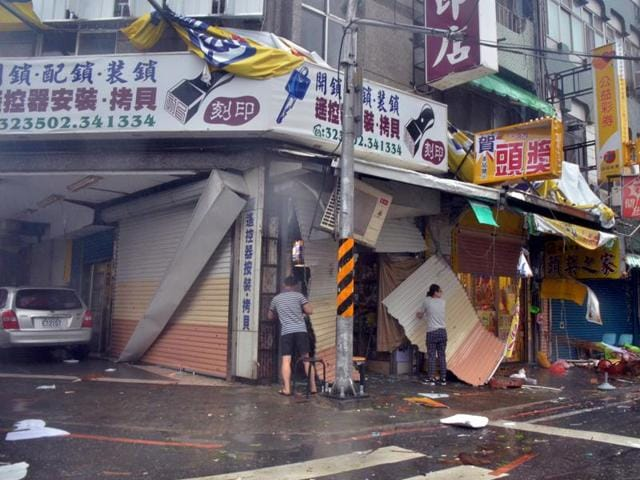 A man and a woman are seen amongst debris in front of a shop with broken shutters, towrn away by strong winds of Typhoon Nepartak in Taitung on July 8, 2016.