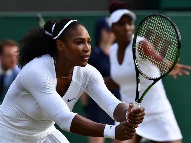 Serena Williams (left) and Venus Williams (right) play against Russia's Ekaterina Makarova and Elena Vesnina during their women's doubles quarterfinal match on the eleventh day of the 2016 Wimbledon Championships at The All England Lawn Tennis Club in Wimbledon.