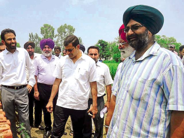 Special investigation team chief Shiv Kumar Verma (centre) checking a plot acquired for the road project at Piplanwala village in Hoshiarpur district on Friday.