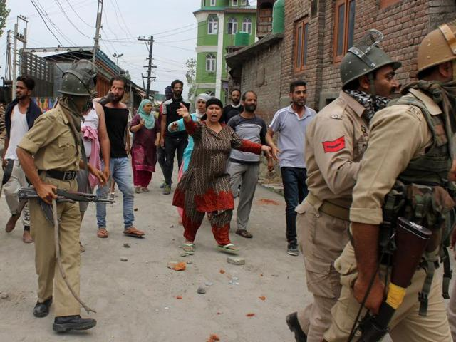 Kashmiris protest as police carry away the body of a youth from outside a hospital in Srinagar.