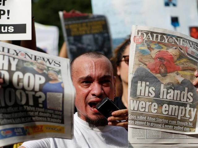 A man shows newspapers as people take part in a protest against the killings of Alton Sterling and Philando Castile during a march in New York.